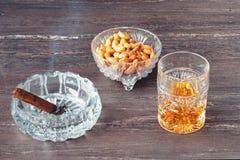 杯威士忌酒、古巴雪茄和坚果在一张灰色木桌上 关闭上色百合软的查阅水 免版税库存图片