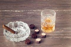 杯威士忌酒、古巴雪茄和巧克力在一张灰色木桌上 关闭上色百合软的查阅水 库存图片