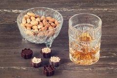 杯威士忌酒、巧克力和坚果在一张灰色木桌上 关闭上色百合软的查阅水 免版税库存图片