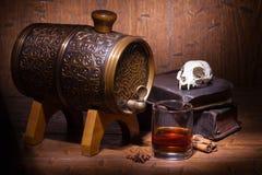 杯威士忌酒、香料、书和小桶 免版税库存图片