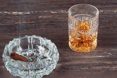 杯威士忌酒和古巴雪茄在一张灰色木桌上 关闭上色百合软的查阅水 免版税图库摄影