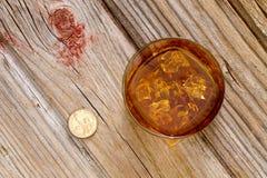 杯威士忌酒和在酒吧柜台的一枚硬币 免版税库存照片