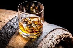 杯威士忌酒和老木桶 免版税库存图片