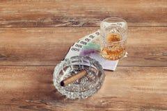 杯威士忌酒和金钱与古巴雪茄在一张灰色木桌上 顶视图 免版税图库摄影