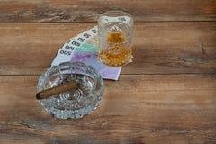 杯威士忌酒和金钱与古巴雪茄在一张灰色木桌上 顶视图 库存图片