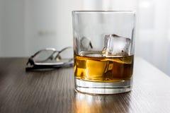 杯威士忌酒,白兰地酒,与冰块的科涅克白兰地在有glassess的木桌书桌上 产品,人的礼物大模型  免版税库存图片