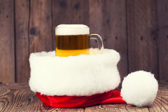 杯子与圣诞老人的帽子的啤酒 库存照片