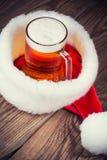 杯子与圣诞老人的帽子的啤酒 免版税图库摄影