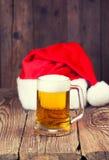 杯子与圣诞老人的帽子的啤酒 免版税库存图片