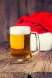 杯子与圣诞老人的帽子的啤酒 图库摄影