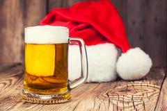 杯子与圣诞老人的帽子的啤酒 免版税库存照片