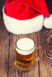 杯子与圣诞老人的帽子的啤酒 库存图片