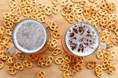 杯子与德国brezel的冷的泡沫似的啤酒 顶上的视图 免版税图库摄影