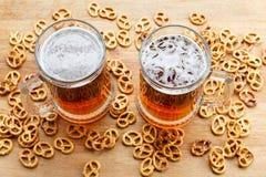 杯子与德国brezel的冷的泡沫似的啤酒 顶上的视图 库存图片