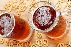 杯子与德国brezel的冷的泡沫似的啤酒 库存图片