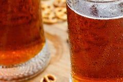 杯子与德国brezel的冷的泡沫似的啤酒 免版税图库摄影