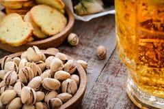 杯子低度黄啤酒和快餐、开心果和油煎方型小面包片在woode 图库摄影
