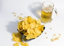 杯子低度黄啤酒,与酥脆土豆片和花生,在白色背景 一顿快的快餐的食物对啤酒 免版税库存图片