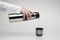 杯子倾吐的热水瓶 库存照片