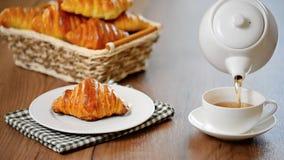 杯子倾吐的茶 早餐用新月形面包 影视素材