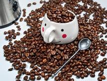 杯子充满咖啡粒在烤咖啡b堆  免版税库存图片