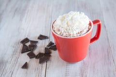 杯子冬天与打好的奶油的热巧克力饮料 免版税图库摄影