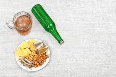 杯子冰镇啤酒、瓶和快餐在轻的木背景 芯片、油煎方型小面包片、咸鱼和花生 图库摄影
