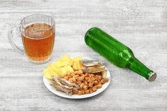 杯子冰镇啤酒、瓶和快餐在轻的木背景 芯片、油煎方型小面包片、咸鱼和花生 库存图片