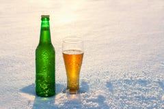 杯子和瓶在雪的冰镇啤酒在日落 背景美好的例证向量冬天 午餐室外重新创建 库存图片