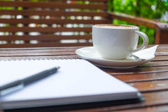 杯子和空的笔记薄咖啡在庭院里 免版税库存照片