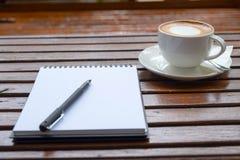 杯子和空的笔记薄咖啡在木桌上 库存照片