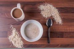 杯子咖啡&碗在一黑暗的木worktop的粥 图库摄影