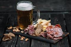 杯子啤酒和快餐在木板 免版税图库摄影