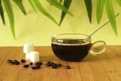 杯子在一个棕色竹木地板上的无奶咖啡与在它和在绿色叶子bac的咖啡豆旁边被堆积的糖片断 免版税图库摄影