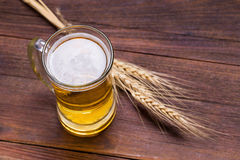 杯子在木桌上的啤酒 皇族释放例证