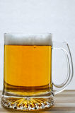 杯子在木头的新鲜的低度黄啤酒 免版税库存图片