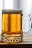 杯子在木头的新鲜的低度黄啤酒 免版税库存照片