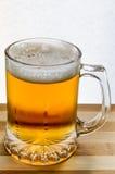 杯子在木头的新鲜的低度黄啤酒 图库摄影