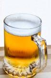 杯子在木头的新鲜的低度黄啤酒 库存图片