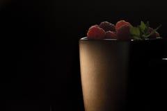 杯子在黑背景的成熟莓 库存图片