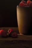 杯子在黑背景的成熟莓 免版税库存图片
