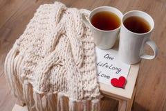 杯子夫妇,背景温暖的围巾,在家庭内部,与文本的餐巾 库存照片