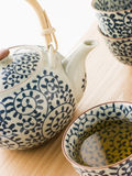 杯子托起绿色日本罐茶 免版税库存照片