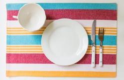 杯子板和利器空的餐位餐具在镶边背景 图库摄影