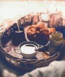 杯子热巧克力、果酱和新月形面包在盘子,一顿早期的早餐在床上 库存照片