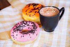 杯子热的可可粉用蛋白软糖和两donats 免版税图库摄影
