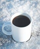 杯子热的咖啡在一张积雪的木桌上的冬天本质上 免版税库存照片
