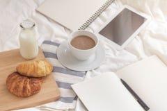 杯子热的牛奶、新月形面包和书在工作表上早晨 库存照片