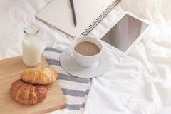杯子热的牛奶、新月形面包和书在工作表上早晨 免版税库存图片