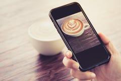 杯子照片在手机屏幕上的热奶咖啡咖啡 库存照片